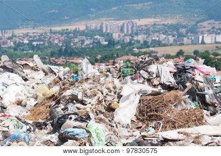 Landfill near small city. Enormous Trash wave near fields