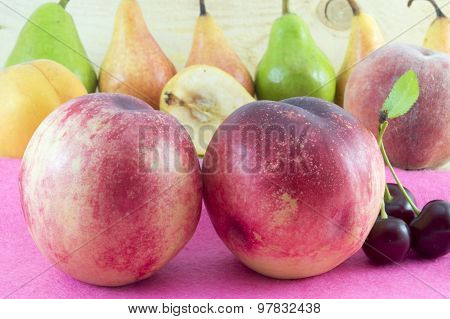 Couple Of Fresh Peaches With Fruit Arrangement In The Background