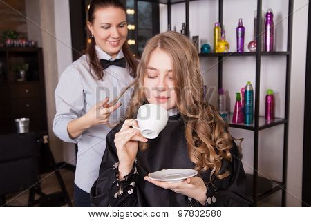 Young woman with coffee cup and hairdresser holding hairspray