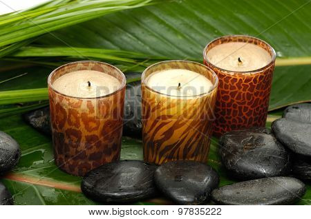 Three candle and stones on wet banana leaf