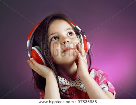 Beautiful little girl listening to music on colour background