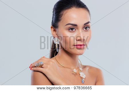 Beauty portrait of pretty woman with fresh skin over gray background. Jewerly concept
