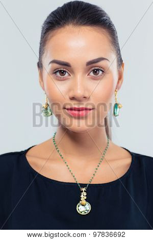Portrait of a happy female model posing over gray background. Jewelry and beauty concept