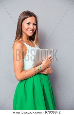 Portrait of a happy beautiful girl holding tablet computer over gray background. Looking at camera