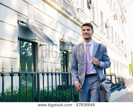 Portrait of a happy businessman walking outdoors in the city