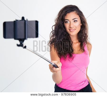 Portrait of attractive young woman making selfie photo on smartphone with stick isolated on a white background