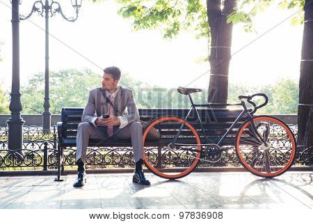 Thoughtful businessman sitting on the bench with smartphone outdoors. Looking away