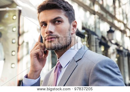 Portrait of a confident businessman talking on the phone outdoors