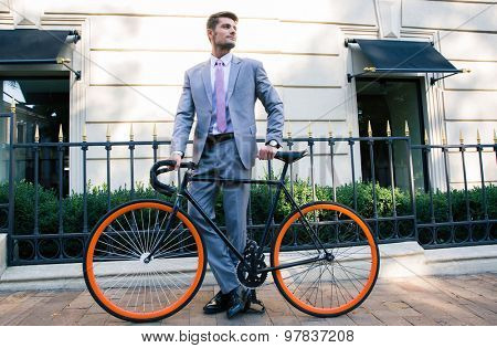 Full length portrait of a handsome businessman standing with bicycle outdoors