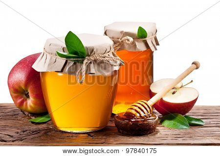 Glass cans full of honey and apples on wood. Clipping paths.