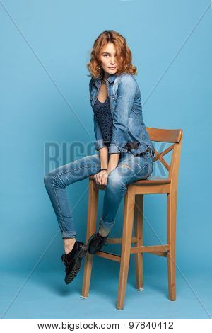 Adult Girl Sitting On A Chair On A Blue Background