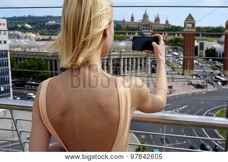 Woman traveler photographing urban view with mobile phone during vacation holidays in summer