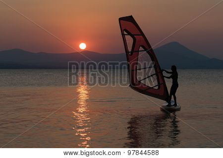 Silhouette of a beautiful woman surfing with her windsurf against the sun.