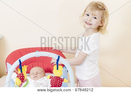 portrait of a little girl with her baby sister sleeping in a chair
