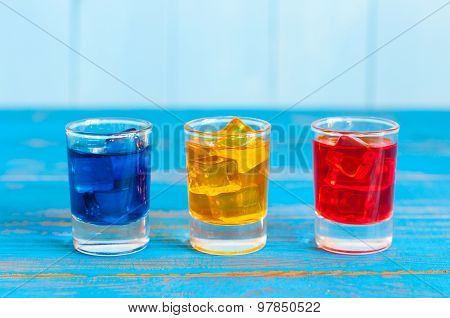 Blue, yellow, rad berry drink or liqueur with ice cube on light background. Cocktail card