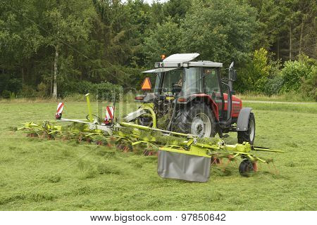 Agriculture, Shaking Of The Mown Grass With Red Tractor With Tedder.