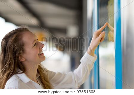 Young Woman Reading A Train Timetable