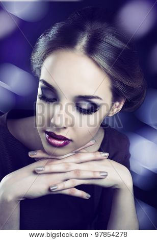 model with bright makeup and retro hair style, against dark studio background