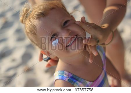 Cute Baby Girl Applying Sun Screen Lotion