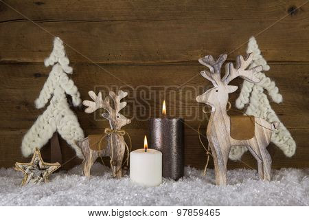Christmas decoration with natural material. Two burning candles with elk and snow on wooden old rustic background.