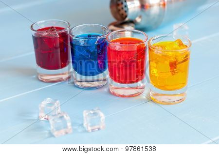 Colorful shot cocktails close up with ice cubes on light bar counter
