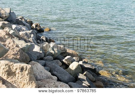 Rocky shoreline and ocean's edge with aqua water