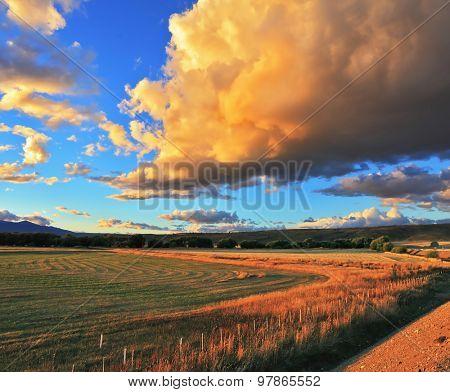 A huge rain cloud lit orange sunset. Cloud covers over the rural field