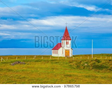 White Chapel. Chapel with red roof on lonely shore of the northern fjord in Iceland
