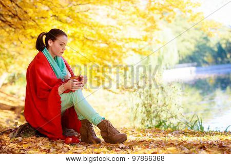 Thoughtful Girl In The Autumn Park Enjoying Hot Drink