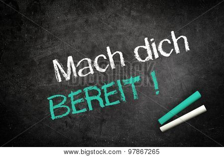 Conceptual Get Ready (Mach dich bereit) Message in German Texts Written on Black Chalkboard with Two Chalks in Lower Right Corner.
