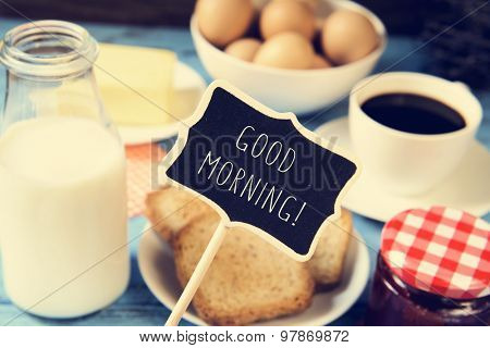 a chalkboard with the text good morning and a blue wooden table with a bottle of milk, a cup of coffee, some toasts in a plate, a jar of jam and a bar of butter
