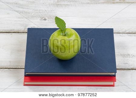 Apple With Books On Top Of Desktop For School