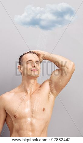 Vertical shot of a handsome young man taking a shower underneath a small raining cloud on gray background