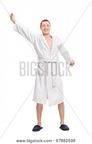 Full length portrait of a cheerful young guy in a white bathrobe stretching himself isolated on white background