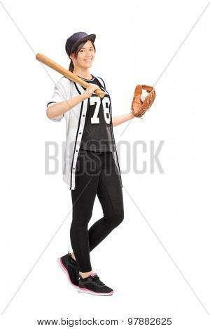 Full length portrait of a young woman in a baseball jersey holding a baseball bat and smiling isolated on white background