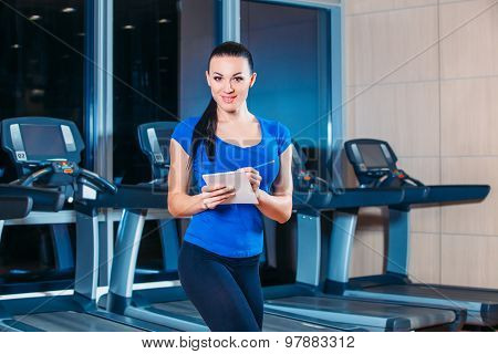 training, fitness, technology and lifestyle concept - Smiling woman with hands in bloktnotom, gym