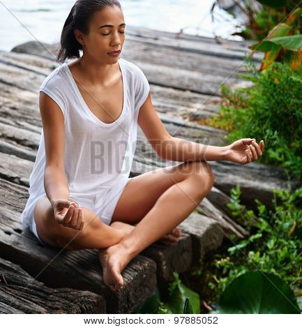 Portrait of a beautiful young woman sitting in yoga pose on a wooden jetty