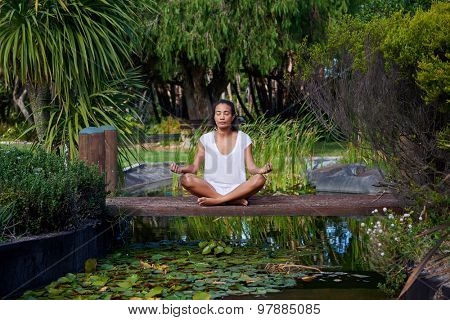 Long shot of a focused young female sitting by a pond, lake, practising yoga