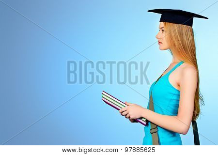 Portrait of a student girl in academic hat standing with books and purposefully looking forward. Copy space.