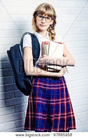 Pretty teen girl wearing school uniform and school bag. Education. Studio shot.
