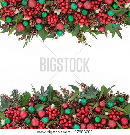 Christmas background border with red bauble decorations, holly, mistletoe, ivy, pine cones and traditional greenery over white.