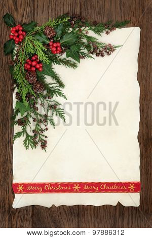 Christmas background border with merry christmas ribbon, holly and winter greenery on parchment paper over old oak wood.
