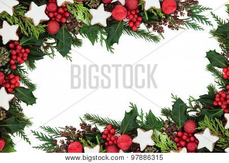 Christmas background border with gingerbread star biscuits, red bauble decorations, holly, ivy, pine cones, cedar cypress and fir over white.