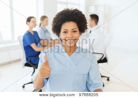 clinic, profession, people and medicine concept - happy  african american female doctor or nurse over group of medics meeting at hospital showing thumbs up gesture