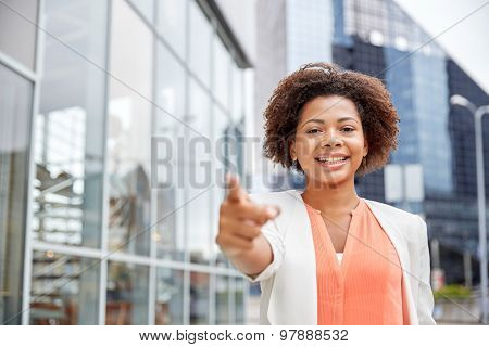 business, gesture and people concept - young smiling african american businesswoman in city pointing finger on you