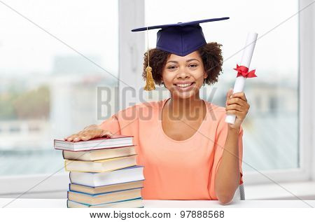 education, school, knowledge, graduation and people concept - happy smiling african american student girl in bachelor cap with books and diploma sitting at table at home
