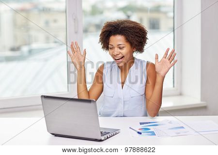 education, business, success and technology concept - happy african american businesswoman or student with laptop computer and papers at office