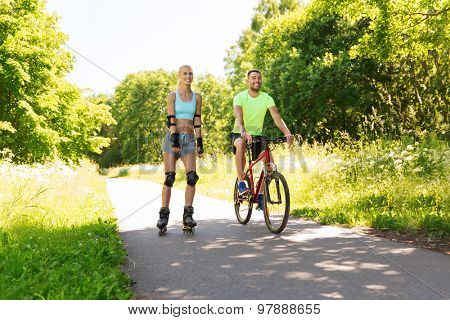 fitness, sport, summer, people and healthy lifestyle concept - happy couple with rollerblades and bicycle riding outdoors at summer