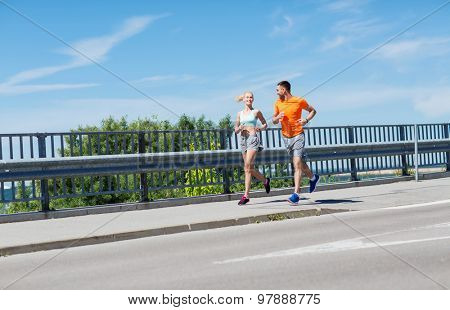 fitness, sport, friendship and healthy lifestyle concept - smiling couple running at summer seaside