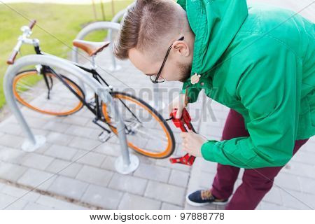 people, security, safety and lifestyle - young hipster man fastening fixed gear bike with blocking lock on city street parking